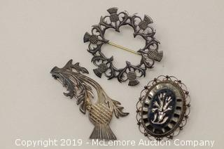Three Assorted Sterling Silver Brooches: Two Are Thistle Themed and One Holds a Hematite